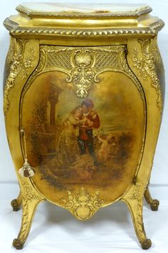 Antique French hand painted and gilded commode depicting a courting scene to front. Intricate scrolled floral relief carving to exterior. Side panels depict a vase and wand. 4 fitted shelves to interior. Locking mechanism to hinged door (key included). 19th century.