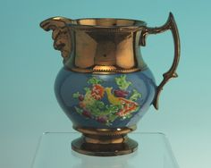 Antique Staffordshire embossed copper lustre jug with yellow bird decoration.  Interesting spout.