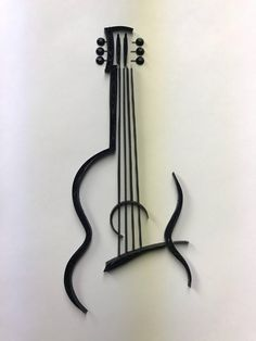 electric guitar tattoo small This is a beautiful silhouette of a guitar, made entirely out of paper. Called quilling, I take small strips of paper and roll and fold them to create one of a kind pieces of art. All come framed and ready to hang. Guitar Wall Art, Guitar Drawing, Wall Drawing, Guitar Painting, Simple Wall Paintings, Wall Painting Decor, Music Tattoo Designs, Music Tattoos, Scrap Metal Art