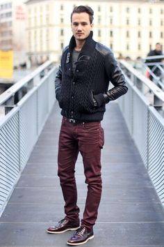 Shop this look on Lookastic:  http://lookastic.com/men/looks/burgundy-jeans-burgundy-brogues-charcoal-crew-neck-t-shirt-black-bomber-jacket/9580  — Burgundy Jeans  — Burgundy Leather Brogues  — Charcoal Print Crew-neck T-shirt  — Black Knit Bomber Jacket
