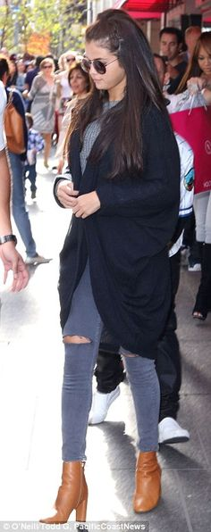 Signature styles: Justin wore baggy trousers while Selena donned a baggy cardigan over jeans
