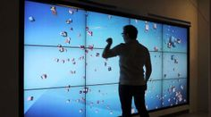 """Testing of our our 12 LCD screen Multi Touch installation in Santa Clara.   The interactive display is a 5464 x 2304 pixel MPE Processing sketch using a number of libraries including Most Pixels Ever to provide multi screen functionality, Traer Physics as the particle system, OpenGL to handle the 3D cube graphics, and TUIOProcessing for multi-touch.  Each sub 46"""" LCD display provides a 1366 x 768 resolution allowing for clear reading of Intel Advertising History content at close proximity.…"""