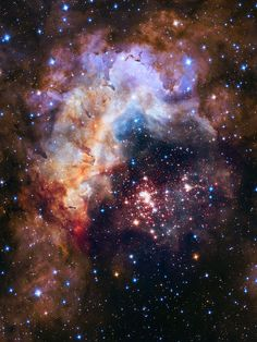 More than 3,000 stars, radiating like cosmic fireworks, lie near the center of this image. The stellar cluster is known as Westerlund 2. The colorful gas cloud above the star cluster is a hotbed of stellar birth known as Gum 29, located 20,000 light-years away from Earth in the constellation Carina.