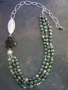 Three Strands of medium sized ivy green coin pearls are offset by a large and faceted nugget of Boulder Opal (stone,) an XL Thai Karen Hill Tribe*