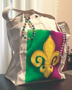 Beautiful hand painted tote bag with Mardi Gras design. Perfect for carrying essentials. beads or anything you may need during the carnival season.