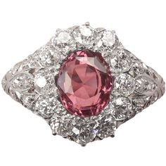 An Edwardian Spinel Diamond Ring. A gold and platinum cluster ring with at the centre an oval cut pink-purplish natural unenhanced spinel surrounded by old cut diamonds (app. 2.14 carats), England, circa 1910.