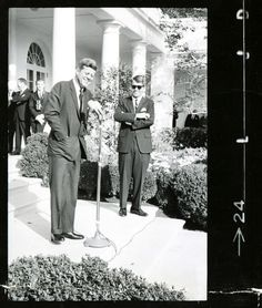 President John F. Kennedy and Robert Kennedy in the White House Rose Garden (1962). Portaritist and photographer Bernie Fuchs is visible in the background with his Rolleiflex twin-lens camera.