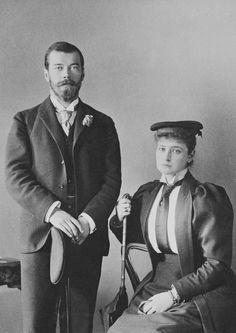 Czarevich Nicholas está virado para a frente em pé; ele usa 3 peças terno e segura seu chapéu. Princesa Alix está sentada à sua esquerda; ela usa terno com camisa, gravata e chapéu. Agosto de 1894.