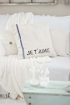 I used a canvas pillow from Canvas Corp, painted some blue lines to resemble a grain sack and stenciled the words 'Je t'aime' using DecoArt paint.