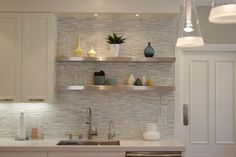 BACKSPLASH!!!  source: Fiorella Design  Contemporary kitchen design with crisp white kitchen cabinets, stainless steel floating shelves, Fucsia 1 Pendants by Flos, Caesarstone quartz countertops and Waterworks Tatami Tiles in Thassos, Ming Green and Celeste backsplash.