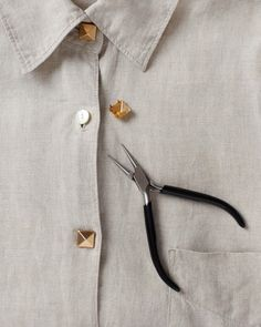 Shirt How-To  Place stud on top of button. Use round needle-nose pliers to fold stud spikes around back of button, securing the stud in place.