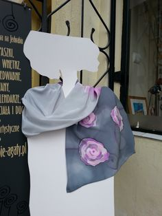 Grey silk scarf with pink roses. Presented on white femine silhouette outside of my workshop. Scarf wrapped around silhouettes neck. Roses stand out against gray background. Hand painted by SilkAgathe.