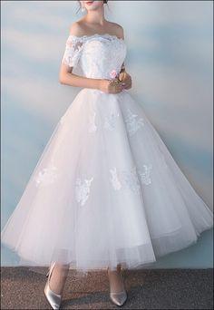 50er Jahre Brautkleid wadenlang geschnitten. Der Tüllrock ist mit Spitzenapplikationen versehen.