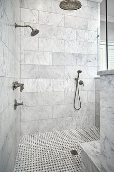 In this beautiful walk-in, zero-entry master bathroom shower, the walls are 12x24 honed White Carrera Marble installed in a traditional subway pattern using larger format tile. The shower floor is a mosaic basket weave using Italian Carrera and the dark tiles are black Absolute Granite to give the pattern a little more detail.