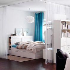 Ce studio regorge de bonnes idées entre les meubles de rangement séparateurs et le lit à double fonction (on y dort et on y range). Ce condensé d'ingéniosité se révèle par ce coin nuit encerclé de rideaux. Plutôt que d'opter pour un paravent un brin classique, les rideaux créent un cocon et font instantanément disparaître le coin nuit.