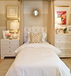 Elegant bedroom design for women with all white bedding and neutral accent pillows lamps and framed pictures. Love the tufted headboard piece that fits perfectly in to the bed's nook against the bedroom wall!