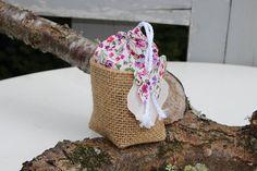 Contenant à dragées en forme de baluchon. Le bas du contenant et en toile de jute. La partie haute est agrémentée par un tissu de coton liberty petites fleurs sur une dominance de couleur rose. Ce petit contenant à dragées est fermé par un galon blanc ou à sa base repos un petit