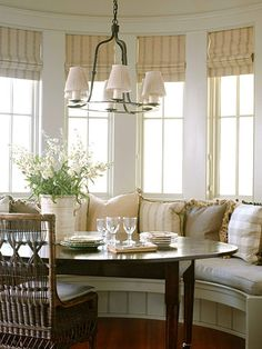 Bay window dining area w/built-in seating, lots of cushions, cane-back chairs  roman blinds. Cozy.