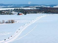 An aerial shot of snowmobilers enjoying a sunny winter day in Aroostook County in Maine.