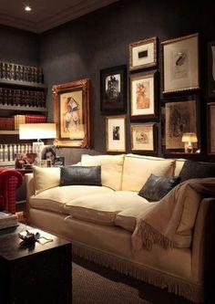 Dark walls, gallery of photos, cream sofa, cozy nest.