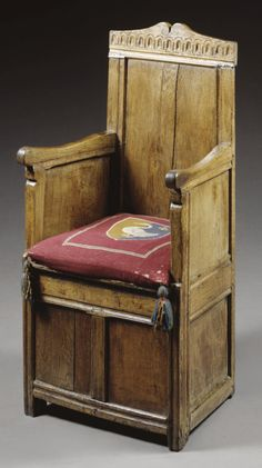 A BOX SEAT ARMCHAIR, CHARLES I, SECOND QUARTER 17TH CENTURY  oak, with panelled back and boarded seat, including a later needlework cushion
