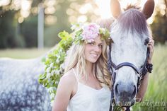 Horse photography session: blonde girl wearing a flower crown and white dress, with her grey gelding wearing a wreath of flowers.