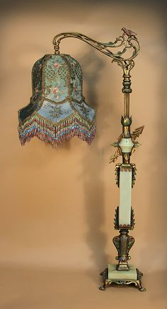 Vintage table top bridge lamp. Made made from ornate metal parts, with a bird in the bridge arm, and three pieces of green jadite glass. Suspended from the arm of a Lotus Bell lamp shade with ombre dyed from light green into blue then covered with gold metallic laces with floral embroidery.  Hand beaded fringe in green, pink and blue colors, is made with hundreds of tiny, pink, antique glass bugle beads at the ends of each strand.