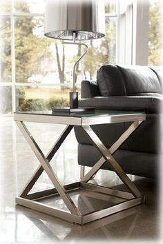 Nickel Color Square End Table - Signature Design by Ashley Furniture by Ashley. $120.32. Made with tubular metal in a brushed nickel color finish. Clear tempered glass top with beveled and polished edge.. Square End Table made with tubular metal in a color finish. Clear tempered glass top with beveled and polished edge. Dimensions:Inches: 22 W x 22 D x 22 H31/14.061 View(List)View Metric: 558.8mm W x 558.8mm D x 558.8mm H Some assembly may be required. Please see product details.