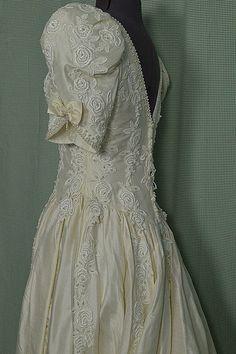 Farbe: weiß  Beschreibung: Dieses exquisite Vintage 1980 Hochzeitskleid ist absolut atemberaubend! Das Kleid verfügt über Polyester Shantung Seide Stoff hat einen schönen Glanz und Textur mit angehoben Threads ausgeführt durch den Stoff. Die elegante Einbauküche Mieder zeigt eine einzigartige V-Form-Ausschnitt vorne und einem tiefen V in den Rücken. Eine komplizierte Konstruktion der Torpedo und rund geformten Kunstperlen trimmt Ausschnitt und kurzen Hocker Ärmel Kanten, die auch mit einem…