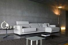 peinture à effet béton brut et canapé blanc cassé avec appui de tête dans le salon
