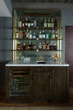 Chic Rustic Wet Bar Boasts Dark Stained Oak Cabinets Fitted With A Glass Door Beverage Fridge Topped White Marble Lined Sink And An Antique