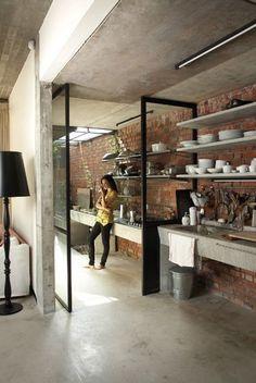 Cozinha integrada com área de serviço decorada com piso de cimento queimado