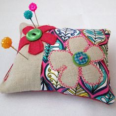 This is a very pretty and feminine pin cushion. It is decorated with appliqued flowers and embellished with cute buttons. We should all have charming flowers somewhere in our sewing box!  I have made this pin cushion in a combination of lovely quality fabrics- printed cotton, plain pink cotton and felt.   This cushion measures approx 21.5cms/5inches across and approx 10cms/4inches in its length.  It is filled with a polyester wadding.  This would make a beautiful addition to your se...