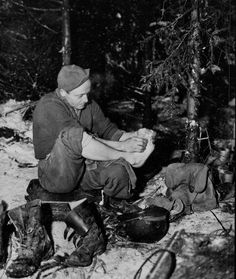 Corporal Lloyd Hood of Concordia, Kansas as tends to his feet in a fighting position outside of Bastogne, Belgium during the Battle of the Bulge. Hood belonged 101st Airborne Division's 327th Glider Regiment, 463rd Parachute Artillery Battalion. January 11, 1945.