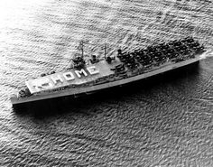 """USS Bataan (CVL 29) photographed on 22 May 1953, as she was en route to Naval Air Station San Diego, California, following a deployment to Korean waters.  Note crew paraded on the flight deck spelling out the word """"HOME"""" and an arrow pointing over her bow. Aircraft on deck include 19 Grumman AF """"Guardian"""" anti-submarine planes and a solitary Vought F4U """"Corsair"""" fighter (parked amidships on the starboard side).   Photo # NH 95808"""