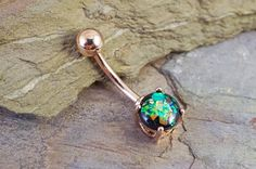 "Synthetic black opal belly button ring. The 8mm black opal is prong set and glows in the light with radiant iridescence. The opal belly ring is 14 gauge and 3/8"" long (10mm), and is made of IP rose go"