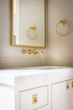 A white single vanity adorned by inset brass pulls is topped with a thick white marble countertop fitted with an undermount sink located beneath a brass faucet fixed on gray grid wall tiles below a gold beveled vanity mirror.