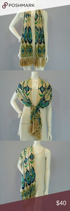 """Great Echo Ikat Pattern Fringed Silk Scarf/Wrap This is a Handsome Echo Silk Scarf 13"""" x 72"""" (includes the great 4.5"""" Fringe.)  It has a Cream Background with an overall Ikat Pattern in Shades of Blue and Green. The silk fringe has a white then a wood bead at the top followed by a 1/2"""" wrap with silk thread. There is both Green and Blue Beading towards the lower quarter on each side. The green beading needs just a little repair (see pic.) Long enough to be very versatile.  Happy to provide…"""
