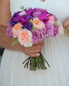 summer wedding bouquet of peach garden roses, lavender coolwater roses, purple dendrobium orchids and purple lisianthus. www.redpoppyfloral.com