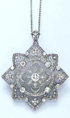 A DIAMOND AND ROCK CRYSTAL PENDANT NECKLACE  The frosted rock crystal pendant, of stylized star design, decorated by old European-cut diamond collets, joined by rose-cut diamond foliate motifs and trim, to the platinum wirework detail, suspended by a 14k white gold link chain, 21¾ ins.