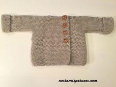 Chaqueta tejida de una pieza adornada con botones de madera. Talla: 3-6 meses. Materiales utilizados: Agujas de punto del número 5. Realizada a punto bobo.