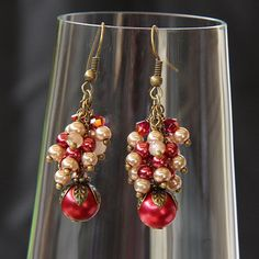 Cluster dangle earrings of little pearl beads in shades of burgundy and champagne above a larger pearl bead