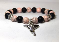 Classic pink and black bracelet. This pretty hummingbird bracelet is made with 8mm pale pink magnesite and matte black onyx with a silver toned hummingbird charm. Simple and Sweet. Black Onyx Properti