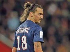Zlatan Ibrahimovic tiene la nariz grande y tiene el pelo largo. Lleva azul oscuro. El es muy alto.