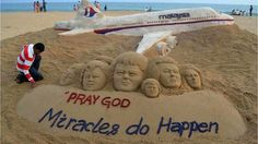 Indian sand artist Sudarshan Patnaik applies the final touches to a sand art sculpture to encourage people to pray for the passengers of Malaysian Airlines flight MH370