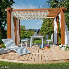 Eine kleine Insel mitten im Garten: Die mit einem Baldachin überdachte Holzterrasse ist eine kleine Liege- Ess- und Relaxoase für heiße Sommertage, an denen …