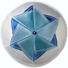 Each wedge of this six panel kippah consists of three elements - white satin base and light and dark blue elements stitched one on top of another. After that all six panels are joined and stitched together making very elegant kippah with distinctive Star of David on top.