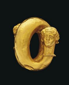 A GREEK GOLD SPIRAL EARRING   LATE CLASSICAL PERIOD, CIRCA 350-320 B.C.   With hollow tapering tubular spiral, the ends terminating in female head protomes, each with hair tied up with a fillet and wearing hoop earrings, and with beaded and plain wire collar  1½ in. (3.7 cm.) high