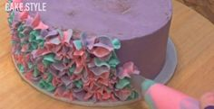 How To Decorate A Tri-Colored Cake With A Star Tip : Piping pink blue and purple frosting flowers onto cake