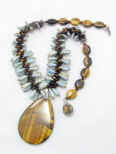 Kumihimo Beaded Necklace with Tiger Eye Pendant. I wove together blue and brown daggers, brown Czech beads and tiger eye beads to form the center. This is by DAKS Design - etsy: